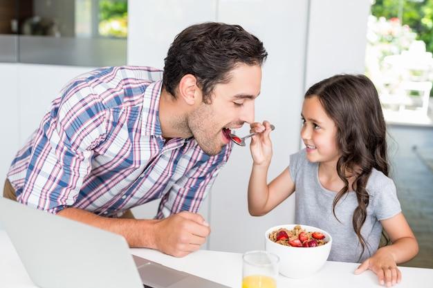Hija sonriente que alimenta la comida al padre