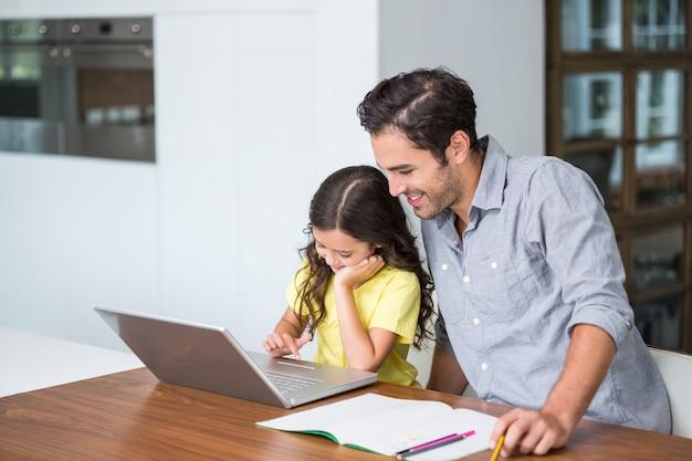 Hija sonriente que trabaja en la computadora portátil con el padre