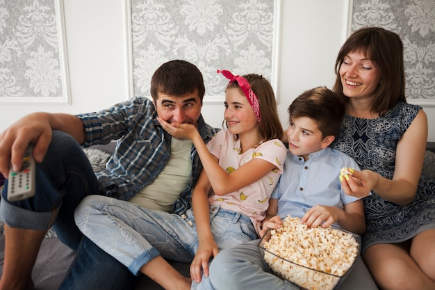 Hija sonriente sentada en el sofá con la familia y alimentando palomitas a su padre