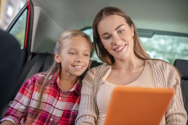 Hija sonriente y su mamá comprobando algo en la tableta en el asiento trasero del coche