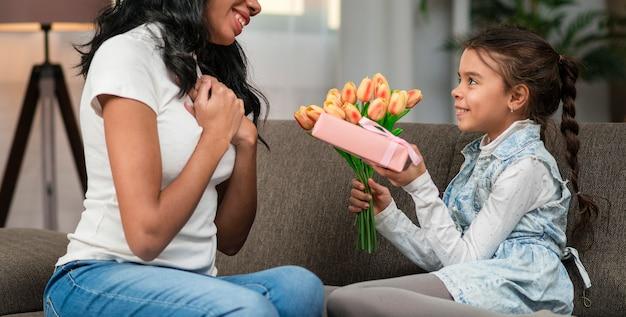 Hija sorprende a mamá con flores y regalos