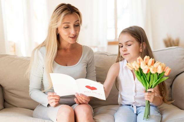 Hija sorprendente madre con flores y tarjeta.