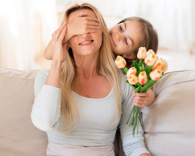 Hija sorprendente madre con ramo de tulipanes