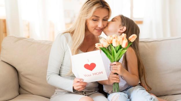 Hija sorprendente madre con tulipanes y tarjeta