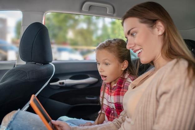 Hija sorprendida y su mamá comprobando algo en la tableta en el asiento trasero del coche
