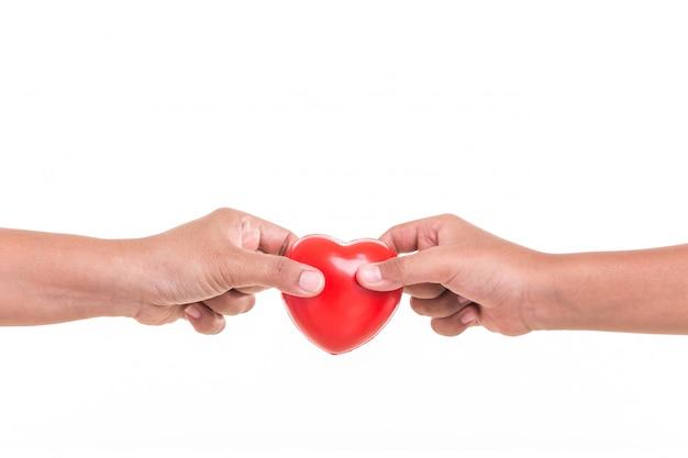 Hija sosteniendo y dando corazón rojo a la mano de su madre aislada en blanco