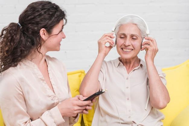 Hija sosteniendo el teléfono móvil mientras su madre escucha música en auriculares