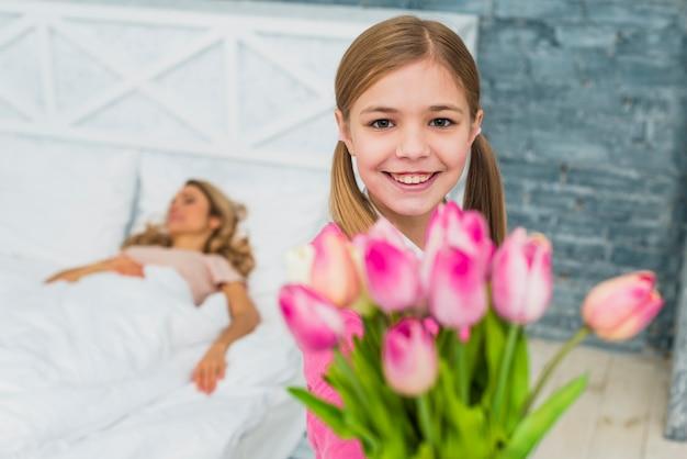 Hija sosteniendo tulipanes para madre dormida