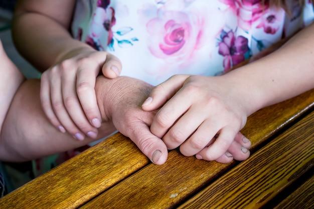 La hija sostiene la mano de la madre en sus manos.
