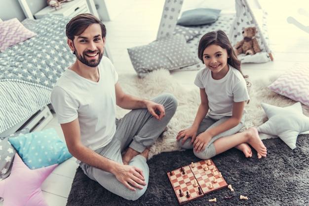 Hija y su apuesto joven papá están jugando al ajedrez.
