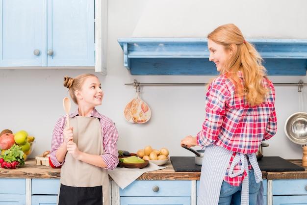 Hija y su madre cocinando comida en la cocina.