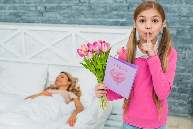 Hija con tulipanes y tarjeta de felicitación sosteniendo el dedo en los labios