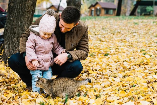 Hija y padre mirando el gato en el parque de otoño