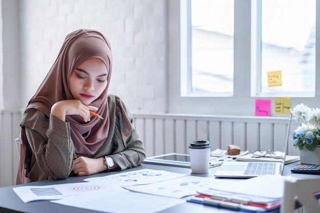 Hijab marrón moderno hermoso de la mujer de negocios árabe que discute datos de la planificación financiera en el lugar de trabajo creativo.