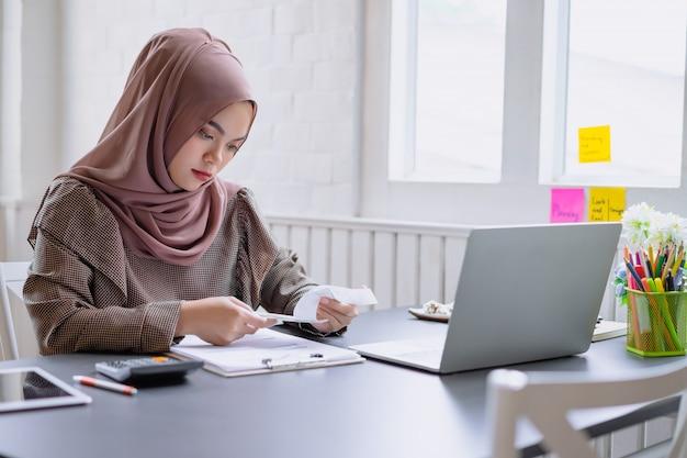 Hijab marrón musulmán hermoso de la mujer de negocios que trabaja sobre financiero con el informe comercial y la calculadora en ministerio del interior.