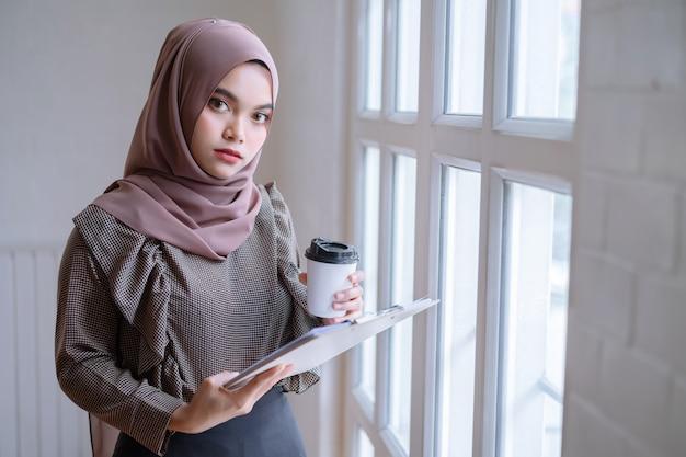 Hijab marrón profesional feliz de la empresaria árabe que trabaja en casa.