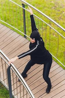 Hijab mujer haciendo ejercicio en el puente de la pasarela temprano en la mañana