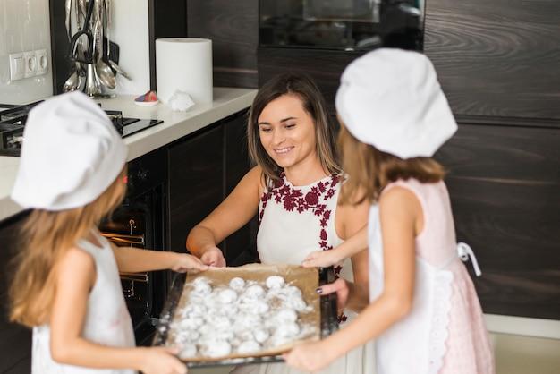 Hijas ayudando a su madre sosteniendo una bandeja para hornear galletas en la cocina.