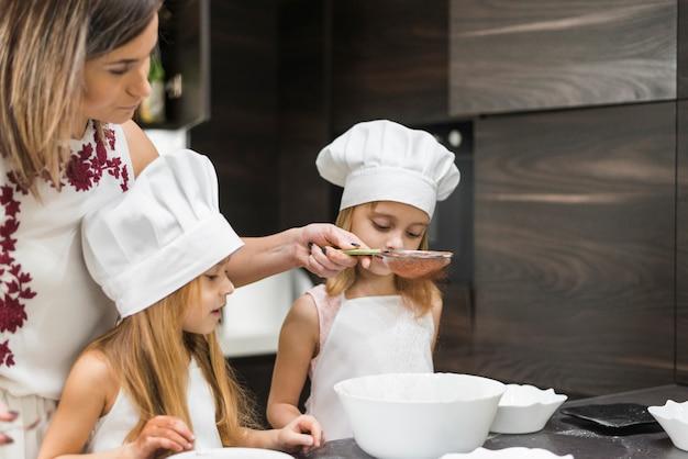 Hijas mirando a la madre tamizar cacao en polvo a través de un colador en la cocina
