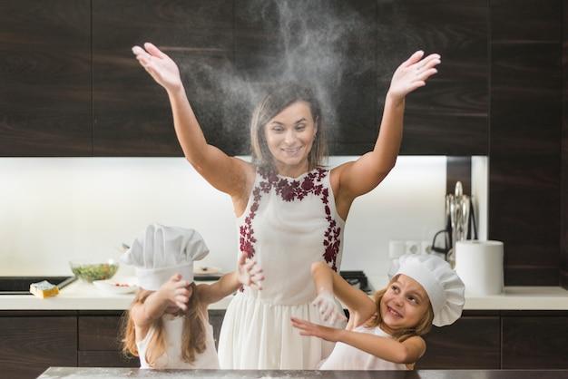 Hijas pequeñas con la madre lanzando harina y divirtiéndose mientras preparan la comida