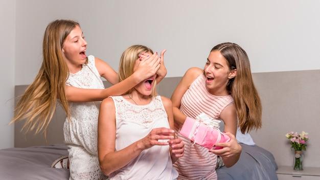 Hijas regalando caja de regalo a madre asombrada.