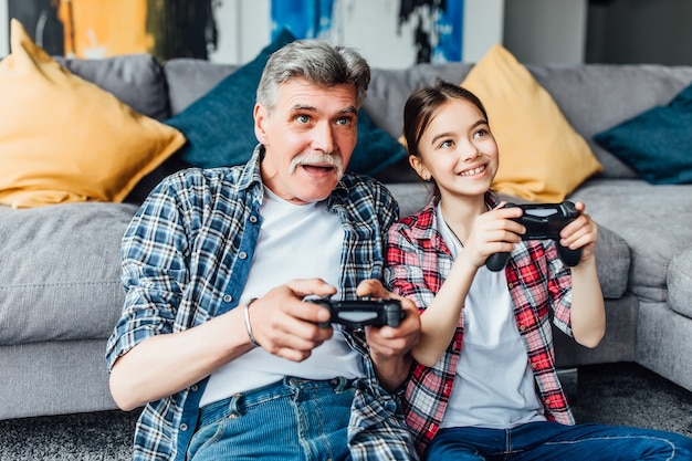 ¡hijita muy sonriente jugando a la consola con el abuelo!