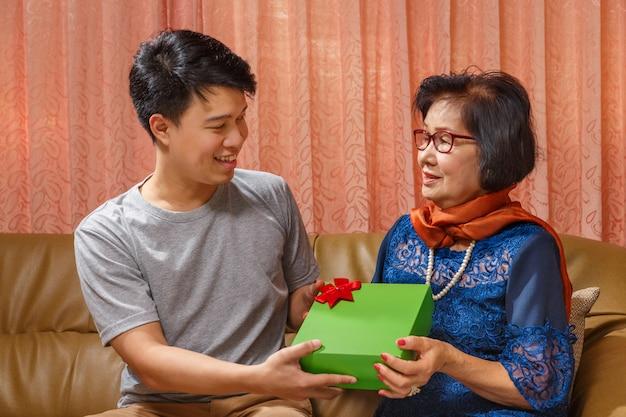 Hijo adulto da un regalo a la madre en el día de la madre.