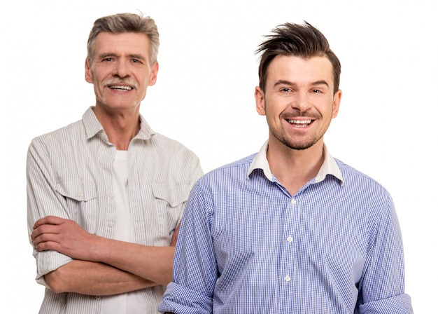 Hijo adulto con padre senior sonriendo sobre blanco