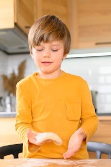 Hijo amasa la masa con las manos desnudas