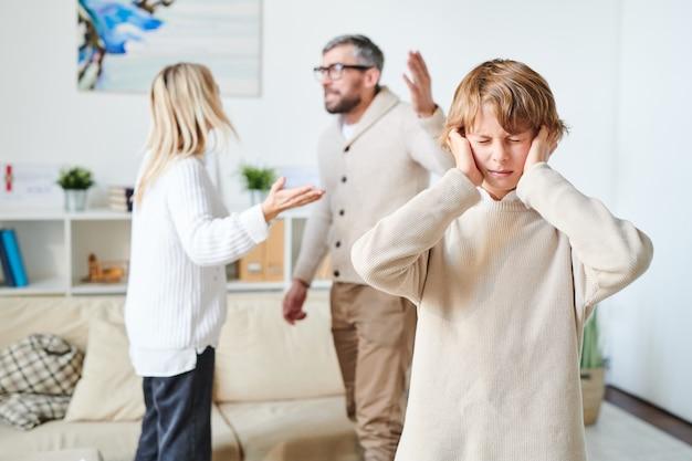 Hijo angustiado que sufre de conflicto de padres