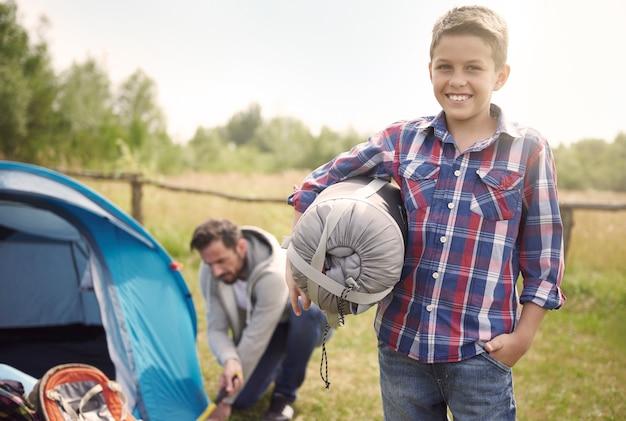 Hijo ayudando a su padre en el camping.