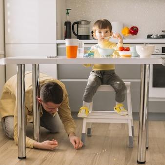 Hijo comiendo y padre limpiando el piso