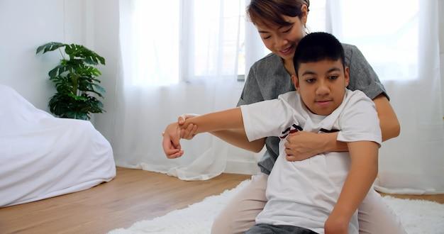 El hijo discapacitado recibe terapia haciendo ejercicio con el apoyo y el cuidado de la madre.