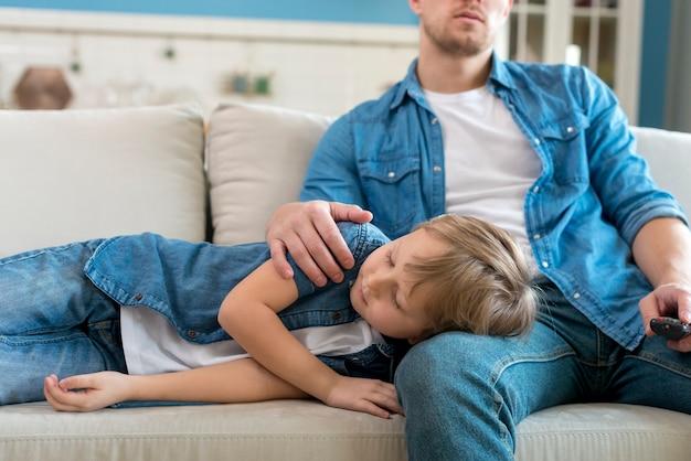 Hijo durmiendo en las piernas del padre