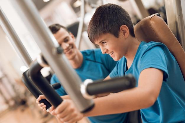 El hijo entrena los músculos pectorales mientras papá está mirando.