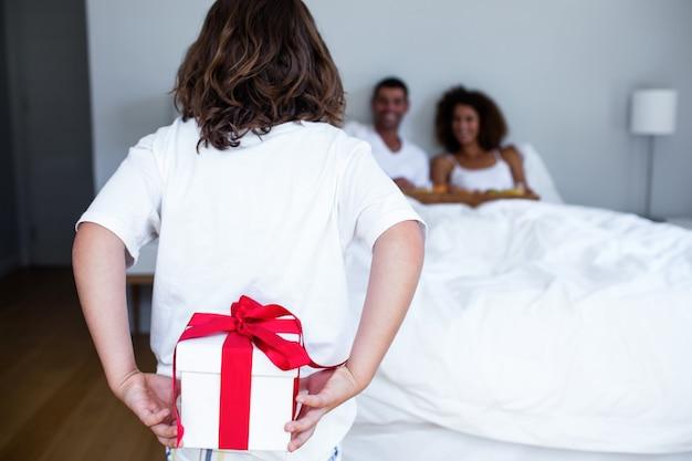 Hijo escondiendo regalo a sus espaldas para padres