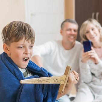 Hijo con espada y padres borrosos