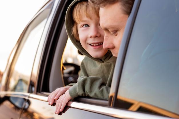 Hijo feliz en el coche con el padre en un viaje por carretera