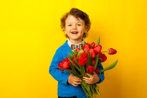 Un hijo feliz, un niño con una chaqueta azul y una mariposa sostiene un enorme ramo de tulipanes rojos