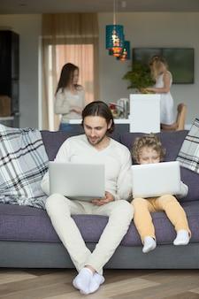 Hijo imitando a padre sentado en el sofá sosteniendo una computadora portátil en casa