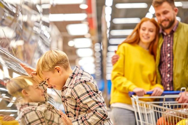 El hijo se inclinó sobre la vitrina en la tienda de comestibles mientras los padres compran juntos, lo miran sonriendo, el niño quiere que los padres compren algo con lo que soñó.