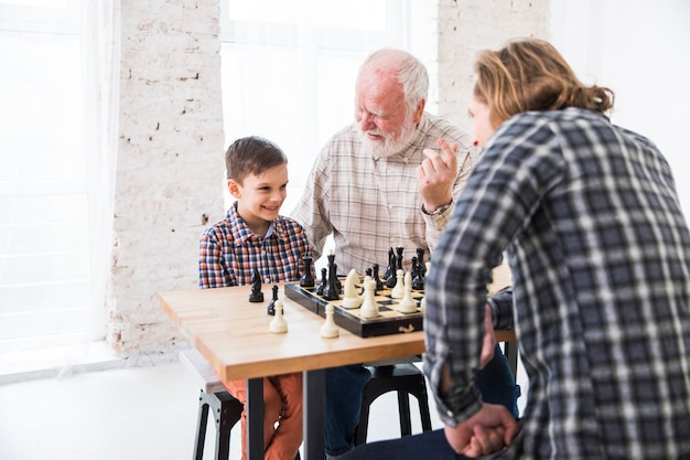 Hijo jugando al ajedrez con papá