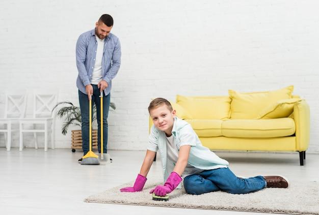 Hijo limpiando alfombra mientras padre usando escoba
