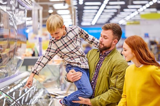 Hijo muestra algo delicioso a los padres en la tienda, quiere que los padres lo compren, señala con el dedo