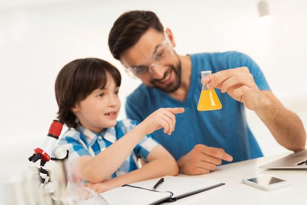 El hijo le muestra a papá un líquido amarillo en un tubo de ensayo.