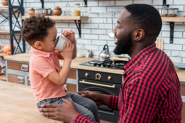 Hijo negro bebiendo té con padre