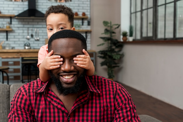 Hijo negro cubriendo los ojos del padre.