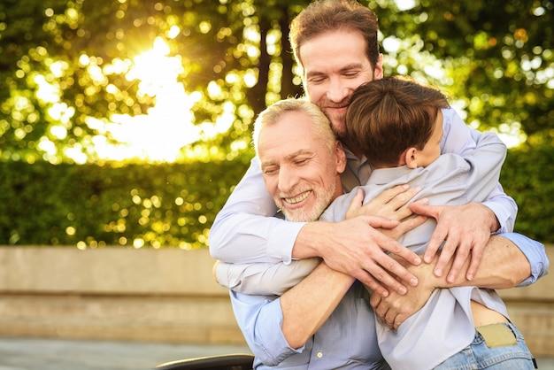 Hijo nieto y anciano abraza reunión familiar
