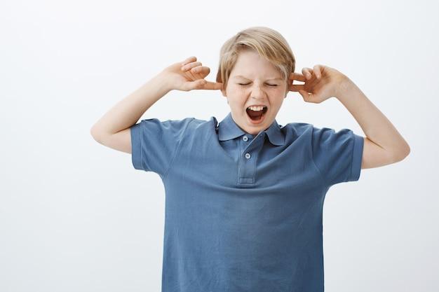 Hijo no quiere ser obediente, hacer ruido y portarse mal. retrato de niño infeliz disgustado de pie