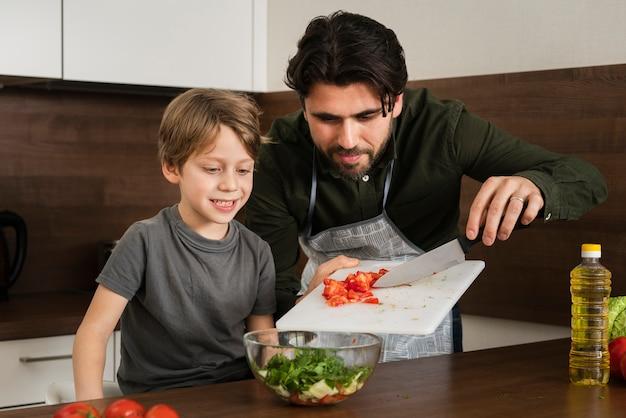 Hijo y padre cocinando ensalada en casa